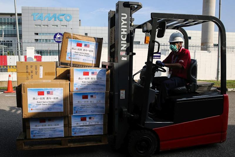 Pharmaniaga staff unload boxes of medical supplies donated by the Chinese Embassy in Shah Alam March 24, 2020. — Picture by Yusof Mat Isa