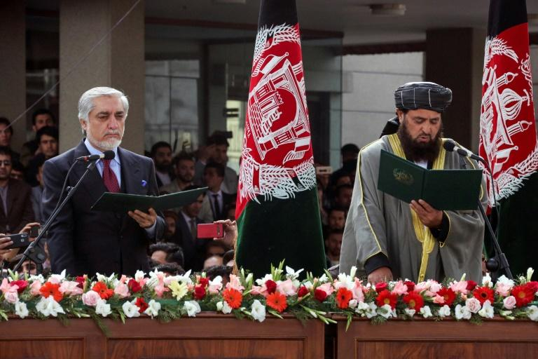 Afghanistan's fomer Chief Executive Abdullah Abdullah (L), takes an oath after vowing to form a parallel government, undercutting the second term of his rival Ashraf Ghani who was sworn in as president