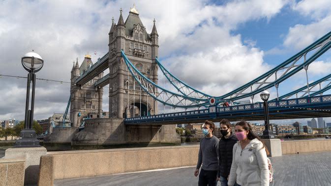 Orang-orang yang mengenakan masker berjalan di tepi Sungai Thames di depan Tower Bridge, London, 6 Oktober 2020. Inggris melaporkan 14.542 kasus terkonfirmasi baru COVID-19, menambah total infeksi di negara itu menjadi 530.113, menurut data resmi yang dirilis pada Selasa (6/10). (Xinhua/Han Yan)