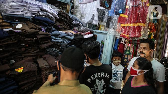 Calon pembeli melihat seragam sekolah di kawasan Pasar Jatinegara, Jakarta, Selasa (30/6/2020). Sejumlah pedagang di tempat itu mengeluhkan omset penjualan seragam sekolah yang menurun hingga 90 persen akibat sepi pembeli dan anjuran belajar di rumah saat COVID-19. (Liputan6.com/Faizal Fanani)