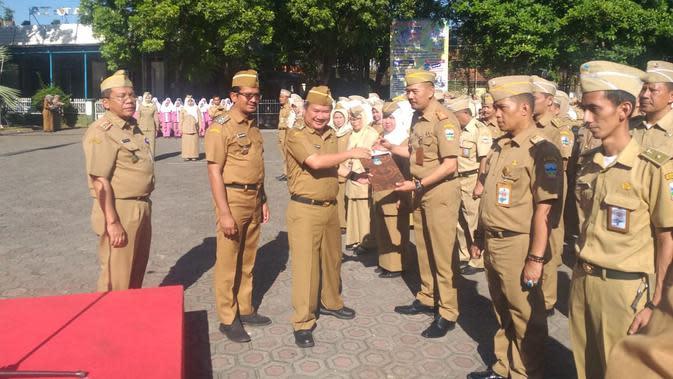 Bupati Garut Rudy Gunawan, tengah menyalami beberapa pejabat berpretasi dalam salah satu acara apel pagi hari Senin di Halaman Setda Garut (Liputan6.com/Jayadi Supriadin)