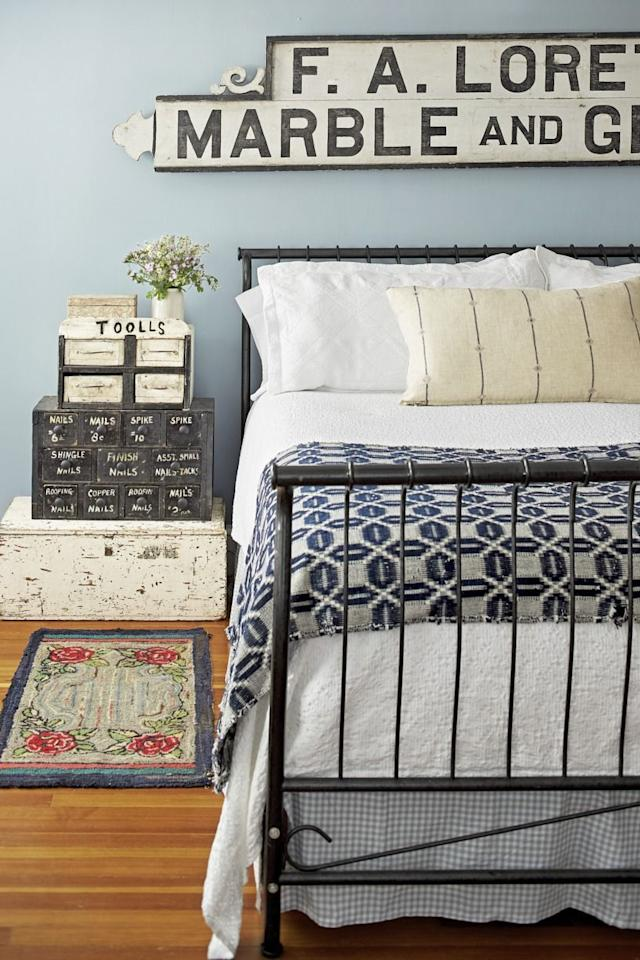 "<p>The found sign hanging above the bed inspired the palette for the guest bedroom. ""I love the scrolling on the sides,"" says homeowner Renita Browning. The sign's black-and-white combo is carried throughout the room, as seen in the bed, bedding, and stacked nightstand comprised of a chippy white trunk and old black toolbox.</p>"