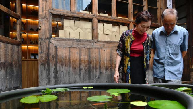 Para pengunjung mengamati ikan mas hias di sebuah museum di Sanfangqixiang (Tiga Jalur dan Tujuh Lorong), Kota Fuzhou, Provinsi Fujian, China, 23 September 2020. Lebih dari 3.000 ikan mas hias dari sekitar 100 spesies dipamerkan di museum tersebut. (Xinhua/Wei Peiquan)