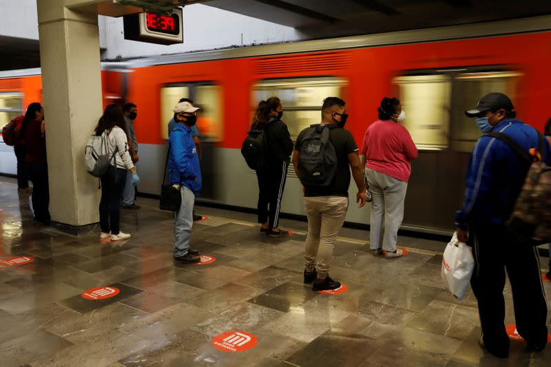 Commuters stand on social distance markers as they wait for the metro, as the government plans to start easing restrictions amid the outbreak of the coronavirus disease (COVID-19) in Mexico City