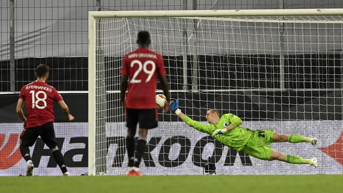 Pemain Manchester United Bruno Fernandes (kiri) mencetak gol lewat tendangan penalti ke gawang Copenhagen pada perempat final Liga Europa di Cologne, Jerman, Senin (10/8/2020). Manchester United menang 1-0. Manchester United menang 1-0. (Sascha Steinbach/Pool via AP)