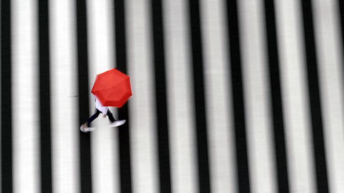 Seorang wanita berjalan di penyeberangan pejalan kaki di tengah hujan di Tokyo, Rabu, (23/9/2020). Badai tropis di Samudra Pasifik perlahan mendekati wilayah Tokyo pada hari Rabu, dan para pejabat mendesak penduduk berhati-hati dari perkiraan hujan lebat dan hembusan angin. (AP Photo/Eugene Hoshiko)