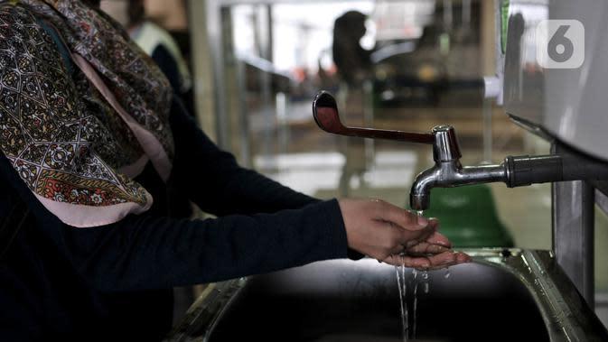 Calon penumpang diwajibkan mencuci tangan sebelum memasuki Terminal Pulo Gebang, Jakarta, Minggu (17/5/2020). Saat ini tercatat hanya ada 38 PO bus yang masih beroperasi dengan batas maksimal mengangkut penumpang mulai 6-10 orang dalam 1 bus. (merdeka.com/Iqbal S. Nugroho)
