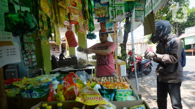 Erdianto (45) pedagang warung sembako tradisional sedang melayani pembeli secara langsung di Pinggir jalan Villa Pamulang, Tangerang Selatan, Banten, Selasa (25/08/2020). (merdeka.com/Dwi Narwoko)