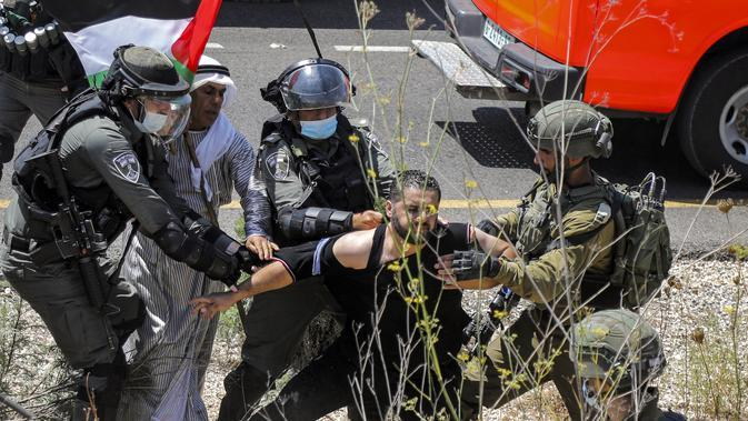 Tentara Israel mengamankan seorang pengunjuk rasa Palestina yang memprotes pembukaan lahan untuk permukiman Israel di dekat Desa Shoufah, wilayah Tepi Barat (20/8/2020). (AFP/JAAFAR ASHTIYEH)