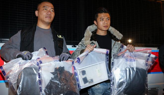Police officers display evidence after two suspected home-made bombs were found at Wah Yan College Hong Kong in Wan Chai. Photo: K. Y. Cheng