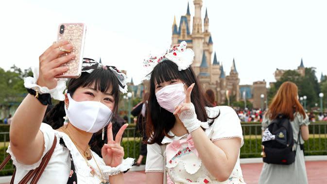 Pengunjung mengenakan masker guna melindungi diri dari virus corona berswafoto saat mengunjungi Tokyo Disneyland di Urayasu, dekat Tokyo, Rabu (1/7/2020). Tokyo Disneyland dibuka kembali untuk pertama kalinya dalam empat bulan setelah sempat ditutup karena penyebaran Covid-19. (AP/ Koji Sasahara)