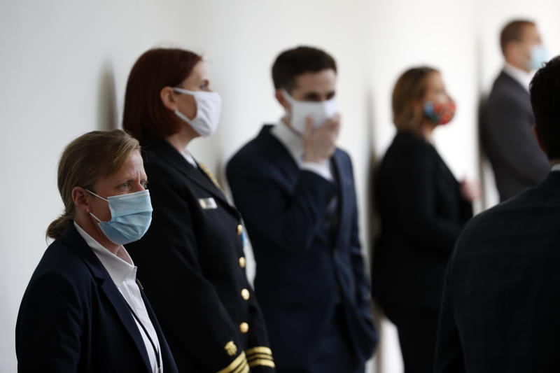 A member of the U.S. Secret Service, front, stands at her post wearing a mask as other staff member social distance wearing masks, before President Donald Trump speaks about the coronavirus during a press briefing in the Rose Garden of the White House, Monday, May 11, 2020, in Washington. (AP Photo/Alex Brandon)