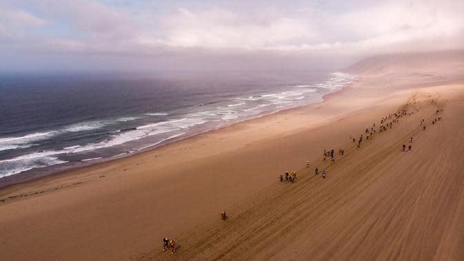Peserta bersaing pada tahap pertama Half Marathon des Sables di Gurun Ica, Paracas, Peru, Senin (2/12/2019). Half Marathon des Sables dibagi menjadi tiga tahap. (Martin BUREAU/AFP)