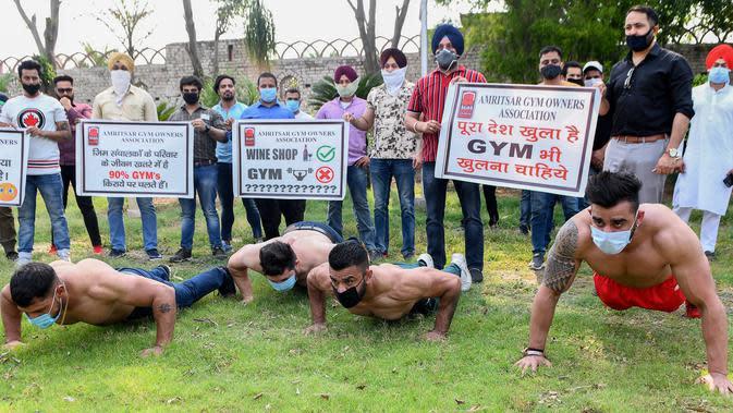 Pemilik dan pelatih gym memegang spanduk saat protes menuntut pemerintah membuka kembali pusat kebugaran di Amritsar, India, Minggu (7/6/2020). Mereka meminta aktivitas tempat olahraga gym juga diizinkan buka setelah pelonggaran lockdown, bukan hanya kegiatan perekonomian. (NARINDER NANU/AFP)