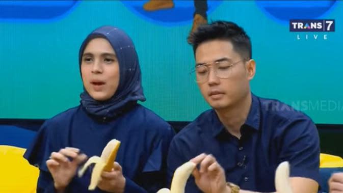 Perempuan yang terkenal dari perannya sebagai Jeng Kellin itu hadir bersama suami, Rizky Kinos. Raffi sebagai pembawa acara mengajak bintang tamunya sama-sama makan pisang dalam acara tersebut. (Youtube/TRANS7 OFFICIAL)
