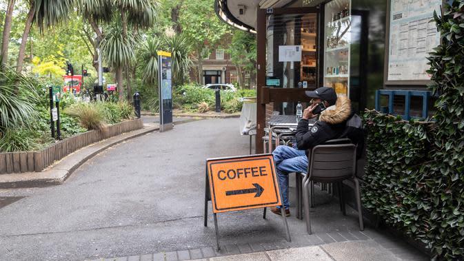 Seorang pria duduk di luar kedai kopi Beatles yang dibuka kembali untuk layanan dibawa pulang (takeaway) di London, Inggris (10/6/2020). Beberapa kedai kopi di Inggris telah dibuka kembali untuk pengiriman atau layanan takeaway dengan mengikuti aturan jaga jarak sosial. (Xinhua/Han Yan)