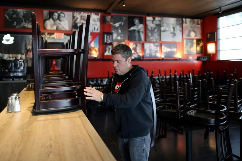 FILE PHOTO: Raul Gonzalez, Jr., 53 stacks chairs at his Mambos Cuban restaurant, which is being forced to close after 32 years, due to the global outbreak of the coronavirus disease (COVID-19), in Glendale