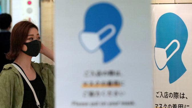 Seorang wanita yang mengenakan masker untuk mencegah penyebaran COVID-19 berjalan di Tokyo, Jepang, Jumat (3/7/2020). Tokyo melaporkan lebih dari 100 kasus baru COVID-19 pada hari 3 Juli 2020. (AP Photo/Eugene Hoshiko)