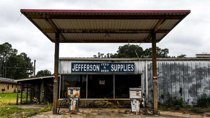 Sebuah pompa bensin sepi terlihat di Fayette, Jefferson County, Mississippi (28/9/2020). Sisa-sisa perkebunan kapas yang berdiri di sana adalah bangunan rapuh yang tersembunyi di antara tumbuhan lebat. (AFP/Chandan Khanna)