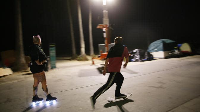 Seorang perempuan bermain sepatu roda di sepanjang trotoar Venice Beach di Venice, California, Kamis (3/9/2020). Menurut data Google, pencarian terkait sepatu roda dari Maret hingga Mei di Amerika Serikat meningkat hampir empat kali lipat. (Mario Tama/Getty Images/AFP)