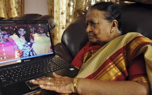 89-year-old Vege Koteshwaramma, looks at the photograph of her granddaughter Nina Davuluri, the first contestant of Indian origin to become Miss America, center on laptop screen, in Vijaywada, 280 kilometers (174 miles) east of Hyderabad, India, Monday, Sept. 16, 2013. (AP Photo)
