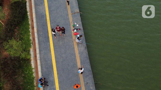 Foto udara memperlihatkan aktivitas warga di pedestrian Danau Sunter, Jakarta, Sabtu (27/6/2020). Beragam aktivitas dilakukan warga sambil menikmati waktu sore di area Danau Sunter, Jakarta. (Liputan6.com/Helmi Fithriansyah)