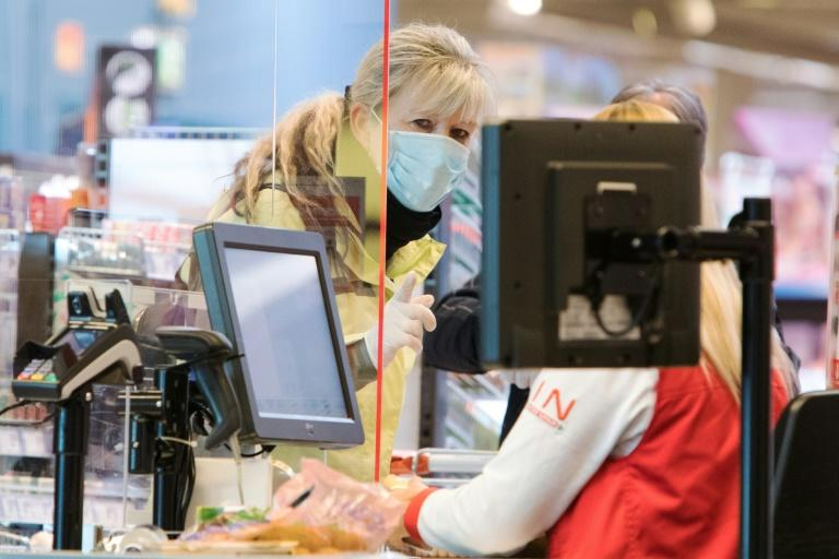 A woman wears a face protection mask at the checkout of a supermarket in Voesendorf near Vienna