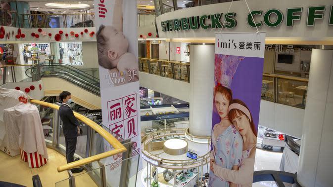 Petugas mengenakan masker melihat pertokoan yang tutup di pusat perbelanjaan, Beijing (3/2/2020). Jumlah korban meninggal dunia di Provinsi Hubei, China tengah, akibat Virus Corona bertambah 65 orang. Hingga Rabu (5/2/2020) pagi, jumlah pasien yang meninggal menjadi 479. (AP Photo/Mark Schiefelbein)