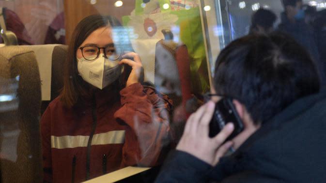Anggota tim medis (kiri) dari Rumah Sakit Xiangya Kedua di bawah naungan Central South University berpamitan dengan anggota keluarganya melalui ponsel sebelum berangkat menuju Wuhan, di Stasiun Kereta Api Selatan Changsha, China, pada 8 Februari 2020. (Xinhua/Chen Zhenhai)