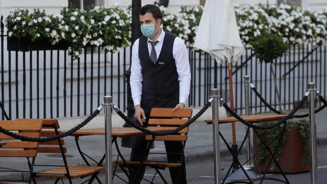 Pramusaji menyiapkan meja dan kursi di ruang makan outdoor di London setelah PM Inggris Boris Johnson mengumumkan serangkaian pembatasan baru, Kamis (24/9/2020). Boris meminta warga Inggris mengikuti aturan pembatasan sosial baru yang akan berlangsung selama enam bulan. (AP Photo/Kirsty Wigglesworth