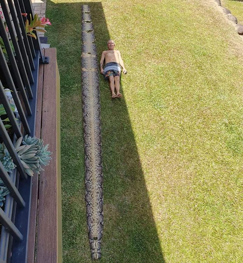 Stuart Morris lays outside a home in Cairns next to a seven-metre snake skin.