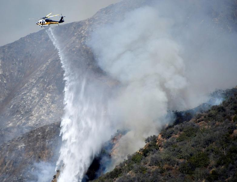 Firefighters battle a blaze from the air that was threatening homes in the Pacific Palisades community of Los Angeles, California, U.S.