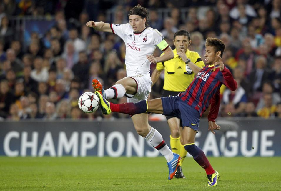 Barcelona's Neymar and AC Milan's Montolivo challenge for the ball during their Champions League soccer match in Barcelona