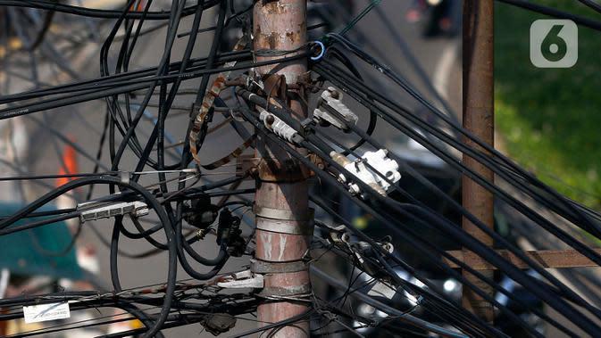 Kabel listrik dan kabel optik yang terlihat semrawut di kawasan Taman Puring, Jakarta, Jumat (3/7/2020). Kesemrawutan kabel ini sering terlihat di sejumlah kawasan Jakarta yang menyebabkan keindahan menjadi hilang dan pemandangan kurang enak untuk dilihat. (Liputan6.com/Johan Tallo)