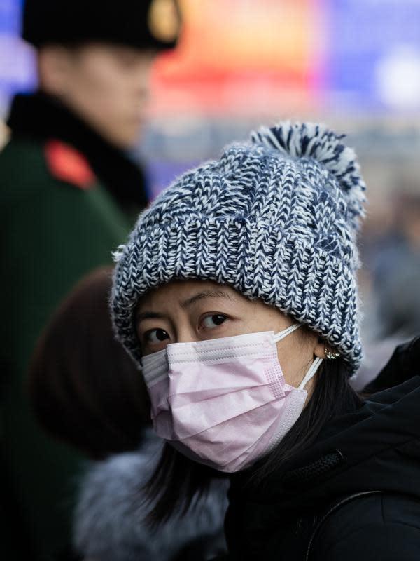 Seorang perempuan mengenakan masker penutup mulut setibanya di stasiun kereta api Beijing untuk mudik Tahun Baru Imlek pada Selasa (21/1/2020). Wabah virus korona seperti SARS yang menyebar di China dan mencapai tiga negara Asia lainnya bisa menular dari manusia ke manusia. (NICOLAS ASFOURI/AFP)