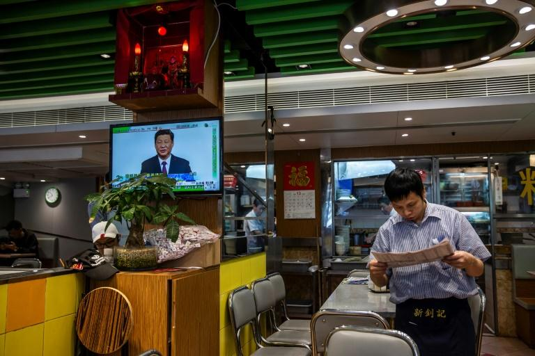 A waiter reads the newspaper as a live broadcast of Chinese President Xi Jinping shows on the television at a Hong Kong eatery in December 2019