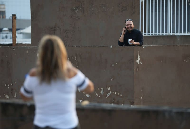 Neighbors talk on the phone from different rooftops during a nationwide quarantine due to the coronavirus disease (COVID-19) outbreak in Caracas