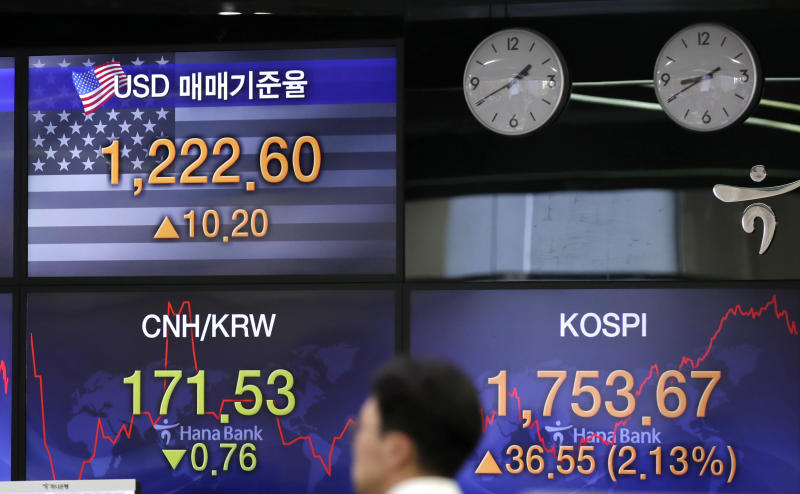 A currency trader walks by the screens showing the Korea Composite Stock Price Index (KOSPI), right, and the foreign exchange rate between U.S. dollar and South Korean won, left top, at the foreign exchange dealing room in Seoul, South Korea, Tuesday, March 31, 2020. Asian shares surged Tuesday after a rally in U.S. stocks, mostly spurred by health care companies' announcements of developments that could aid in the coronavirus outbreak. (AP Photo/Lee Jin-man)
