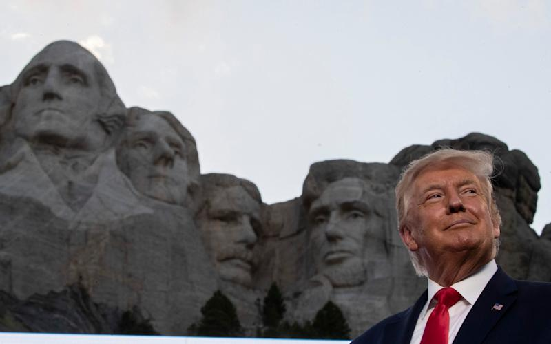 President Donald Trump smiles at Mount Rushmore National Memorial - AP