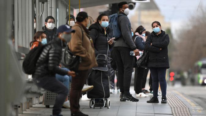 Orang-orang menunggu trem di Stasiun Flinders Street pada hari pertama wajib masker di tempat umum, di Melbourne, Kamis (23/7/2020). Penduduk kota terpadat kedua di Australia, Melbourne, diwajibkan mengenakan masker ketika meninggalkan rumah untuk mencegah penyebaran COVID-19. (William WEST/AFP)