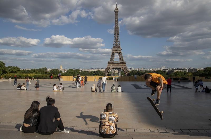 FILE - In this Monday, May 25, 2020 file photo, people stroll at Trocadero square near the Eiffel Tower in Paris. European Union envoys are close to finalizing a list of countries whose citizens will be allowed back into Europe once it begins lifting coronavirus-linked restrictions. The United States appears almost certain not to make the list, as new infections surge and given that President Donald Trump has imposed a ban on European travelers. (AP Photo/Michel Euler, File)