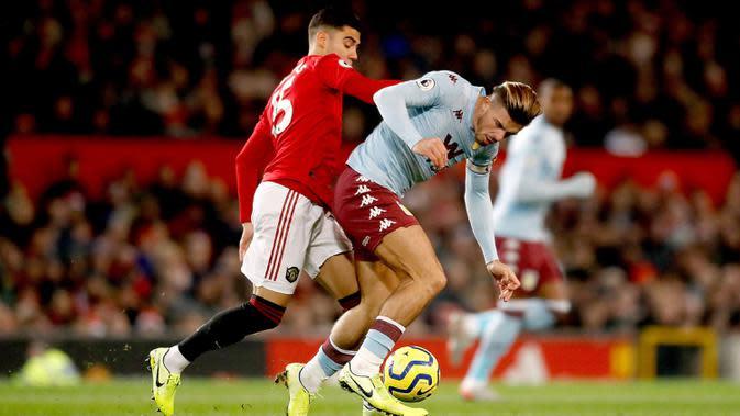 Pemain Manchester United Andreas Pereira (kiri) berebut bola dengan pemain Aston Villa Jack Grealish saat bertanding pada pertandingan Liga Inggris di Old Trafford, Manchester, Inggris, Minggu (1/12/2019). Skor berakhir 2-2. (Martin Rickett/PA via AP)