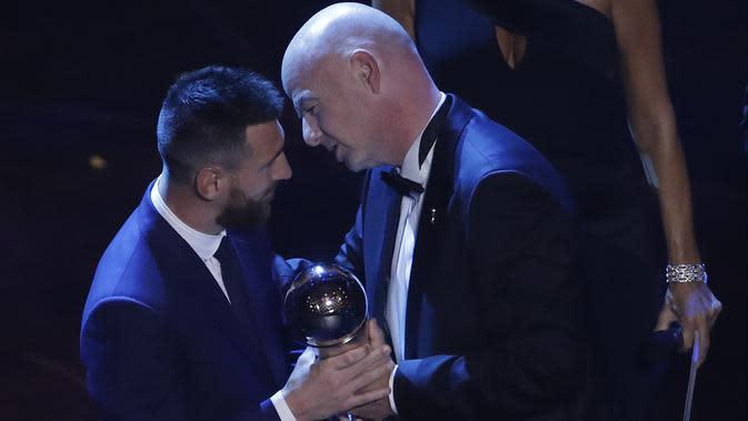 Penyerang Barcelona, Lionel Messi saat menerima penghargaan Pemain Terbaik Dunia 2019 versi FIFA dari presiden Gianni Infantino di teater La Scala Milan, Italia utara (23/9/2019). (AP Photo/Antonio Calanni)