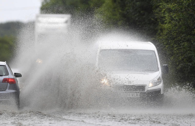 Cars make their way through standing water on a main road near Peterborough, England, after heavy rain fell overnight, Sunday July 28, 2019. Weather forecasters have issued a yellow weather warning for rain across and possible travel disruption in many parts of England on Sunday. (Joe Giddens/PA via AP)