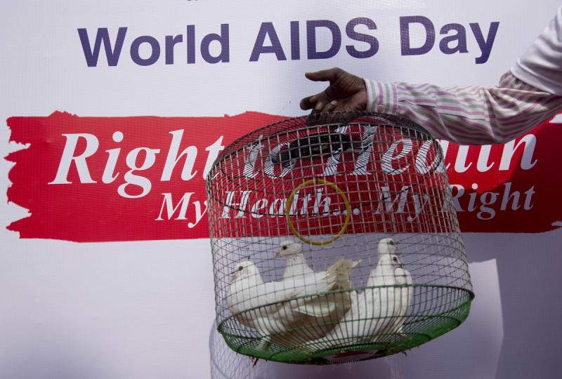 An Indian volunteer holds a cage of pigeons before releasing them during an awareness procession to mark the World AIDS Day in Hyderabad, India, Friday, Dec. 1, 2017. World AIDS Day is observed every year to raise people's awareness in the fight against HIV. (AP Photo/Mahesh Kumar A.)