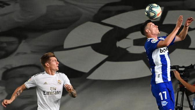 Gelandang Real Madrid, Toni Kroos (kiri) berusaha merebut bola dari bek Alaves, Adrian Marin Gomez pada lanjutan Liga Spanyol di stadion Alfredo di Stefano, Sabtu (11/7/2020). Real Madrid menang 2-0 lewat gol Karim Benzema dan Marco Asensio. (GABRIEL BOUYS/AFP)
