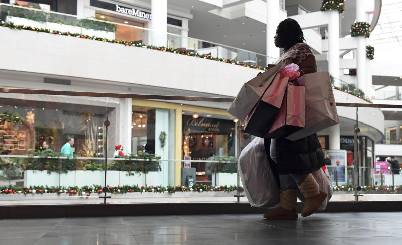 FILE - In this Dec. 22, 2017, file photo a woman shops at the Pentagon City Mall in Arlington, Va. Clothing retailers, particularly those in malls, have been devastated by changing consumer behavior. More than 9,000 stores were shuttered last year. (AP Photo/Susan Walsh, File)