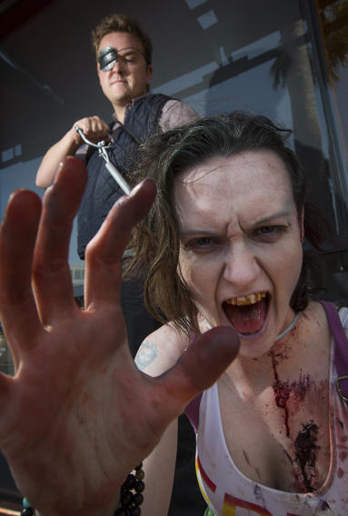 """Cosplayers husband and wife duo pose dressed as the Governor and a zombie respectively from """"The Walking Dead"""" television and comic series during the 2013 San Diego Comic-Con International"""