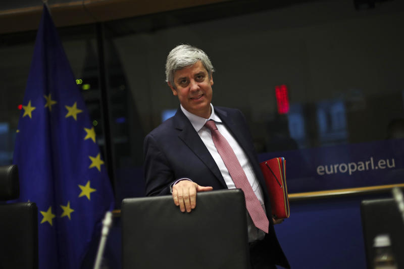 """FILE - In this Monday, Nov. 18, 2019 file photo Eurogroup President Mario Centeno arrives to a Committee on Economic and Monetary Affairs at the European Parliament in Brussels. Governments from the 19 countries that use the euro overcame sharp differences to agree Thursday on measures that could provide more than a half-trillion euros ($550 billion) for companies, workers and health systems to cushion the economic impact of the virus outbreak. Mario Centeno, who heads the finance ministers' group from euro countries, called the package of measures agreed upon """"totally unprecedented... Tonight Europe has shown it can deliver when the will is there.""""(AP Photo/Francisco Seco, File)"""