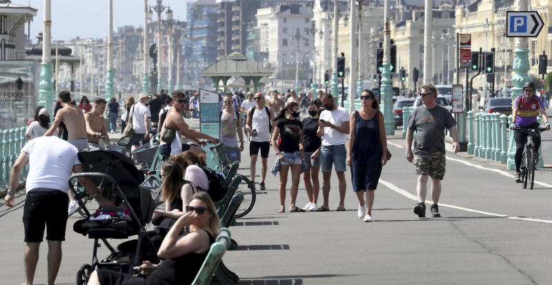 People on the promenade during the warm weather in Brighton in East Sussex, England as the UK continues in lockdown to help curb the spread of the coronavirus, Saturday May 9, 2020. (Gareth Fuller/PA via AP)